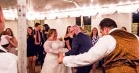 Best man dancing by himself behind the bride and groom.